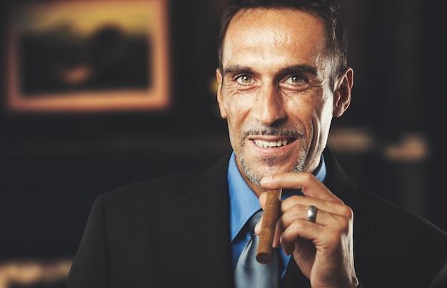 Mature homme d'affaires fumant un cigare dans une chambre élégante