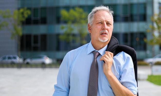 Mature homme d'affaires marchant en plein air dans un cadre urbain moderne