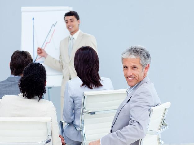Mature homme d'affaires souriant à la caméra lors d'une conférence
