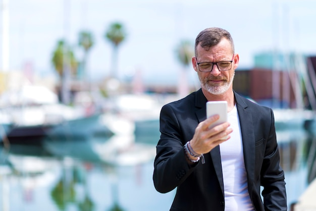 Mature, homme affaires, utilisation, téléphone portable, debout, dehors, contre, port