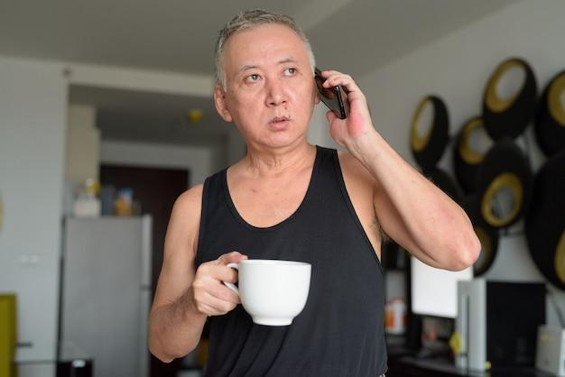 Mature homme japonais tenant un café tout en parlant au téléphone à la maison