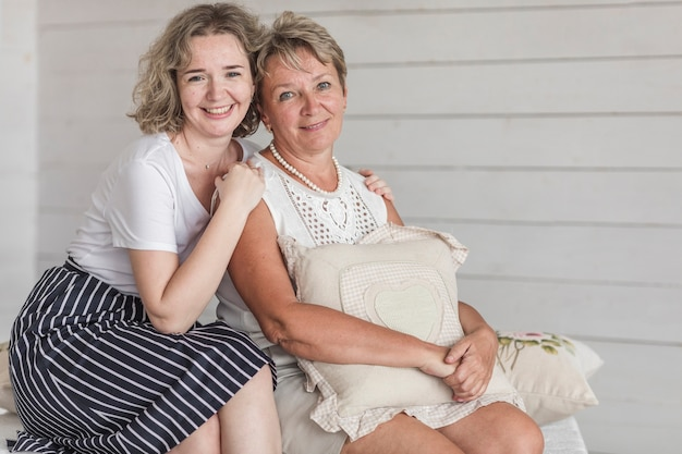 Mature mère souriante tenant un coussin assis avec sa belle fille