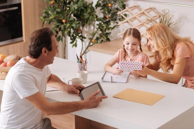 Mature souriant beau père bénéficiant de vacances en famille à la maison et à l'aide de tablette tandis que femme donnant cadeau à la fille