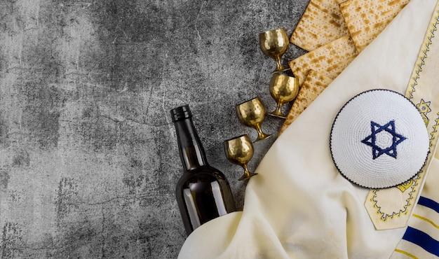 Matzoh, assiette de seder en argent et vin casher à quatre coupes pour fond de pâque juive.