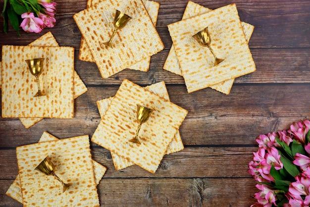 Matzoh juif avec des tasses de vin sur fond rustique en bois. concept de vacances de la pâque.