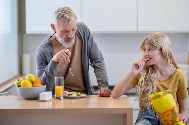 Mauvais appétit. papa essaie de faire prendre le petit déjeuner à sa fille
