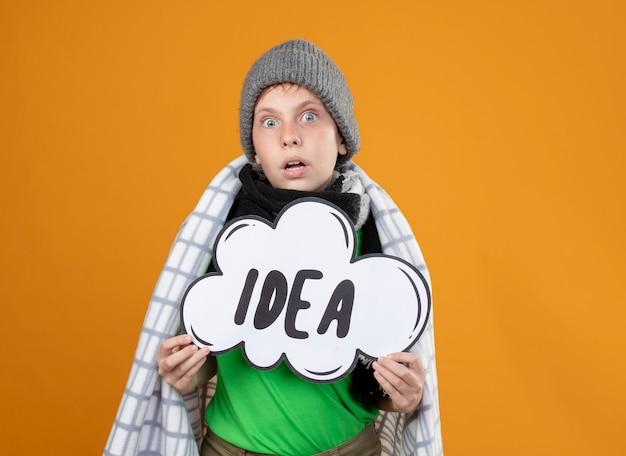 Mauvais petit garçon portant un chapeau chaud et une écharpe enveloppée dans des couvertures montrant le signe de la bulle avec le mot idée à être surpris debout sur le mur orange