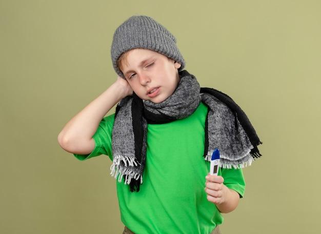 Mauvais petit garçon portant un t-shirt vert en écharpe chaude et un chapeau se sentant mal tenant un thermomètre regardant la caméra malheureux et malade debout sur fond clair