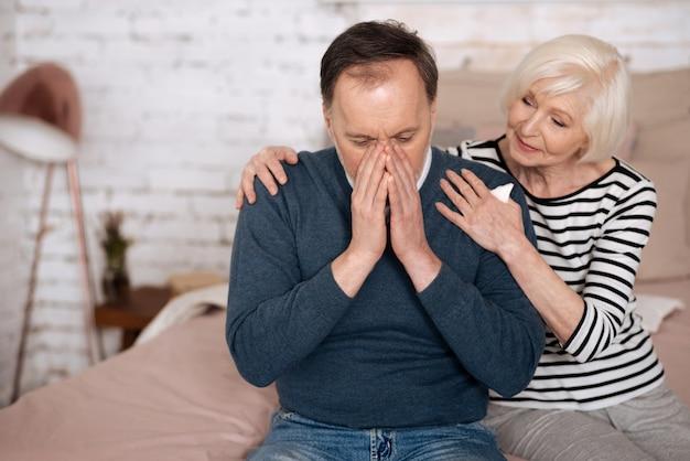 Mauvaise allergie. le vieil homme se couvre le visage en éternuant et sa femme aînée le soutient.