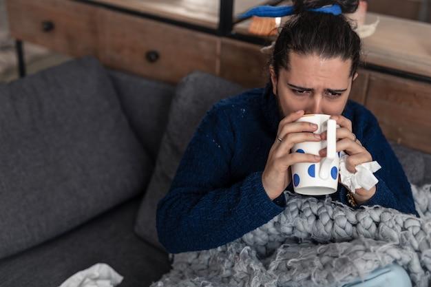 Mauvaise maladie. vue de dessus d'un homme malade triste buvant du thé à la maison