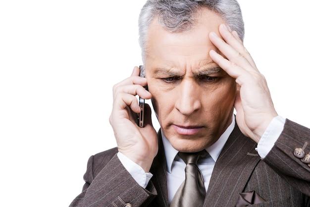 Une mauvaise nouvelle inattendue. portrait d'un homme mûr frustré en tenue de soirée tenant le téléphone portable en se tenant debout sur fond blanc