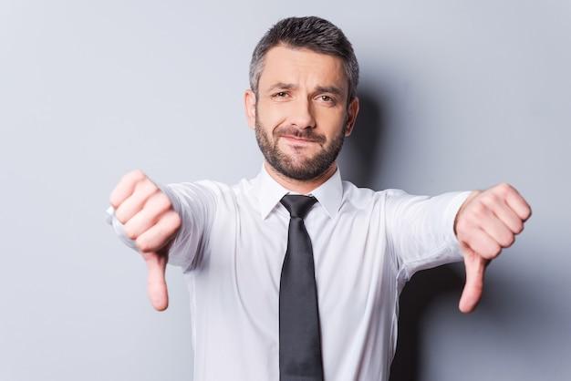 Mauvaise nouvelle pour vous ! homme mûr en chemise et cravate montrant ses pouces vers le bas en se tenant debout sur fond gris
