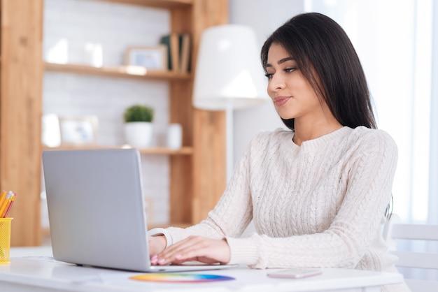 Mauvaise proposition. belle charmante pigiste féminine utilisant un ordinateur portable et posant à table