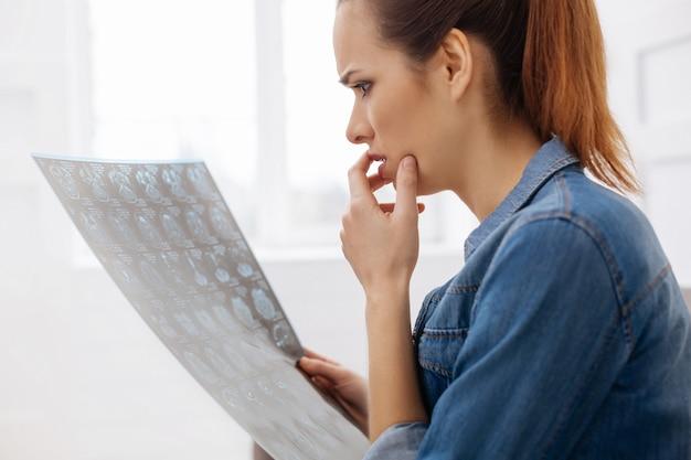 Mauvaises nouvelles. jeune femme anxieuse dérangée examinant son scanner cérébral après que le médecin ait souligné les problèmes et réfléchi au traitement