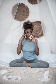 Mauvaises nouvelles. triste femme à la peau sombre qui pleure dans les vêtements à la maison, parler sur smartphone avec serviette près du visage assis sur le lit