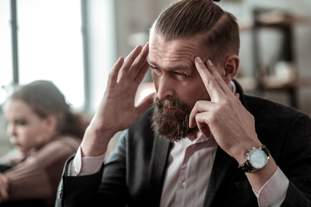 Maux de tête après conflit. père barbu aux cheveux noirs ayant des maux de tête après un conflit avec sa fille adolescente