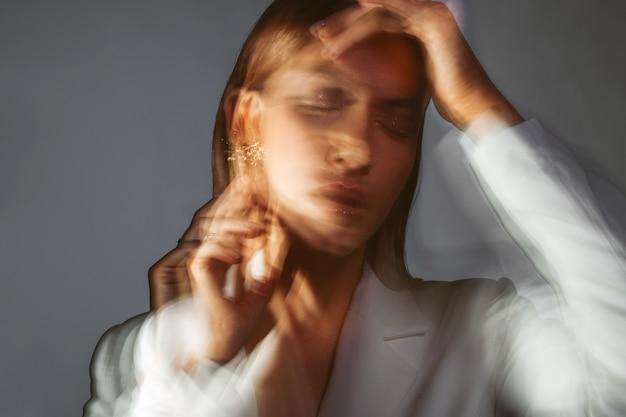 Maux de tête et concept de santé mentale une jeune femme élégante dans une veste blanche