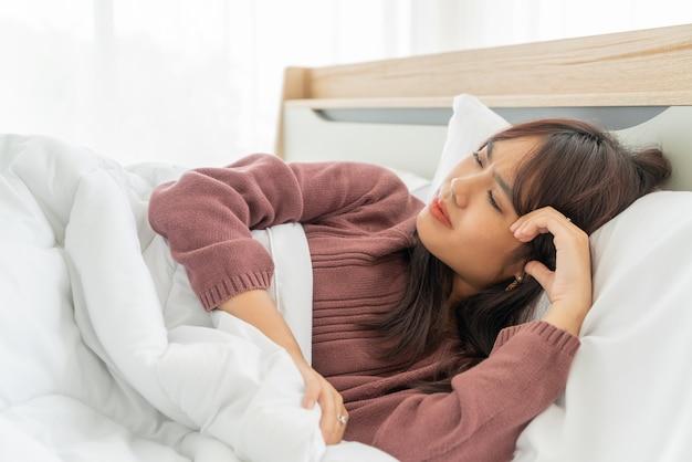 Maux de tête de femme asiatique et dormir sur le lit