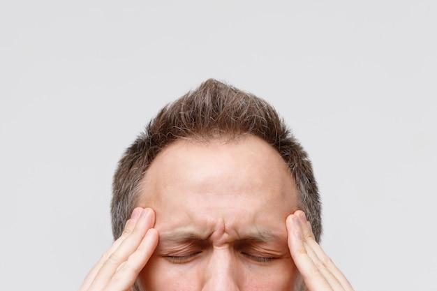 Maux de tête, tension nerveuse, concept de douleur temporelle et lancinante. bouchent le portrait d'un homme massant ses tempes, les yeux fermés, isolé sur fond gris. migraine forte