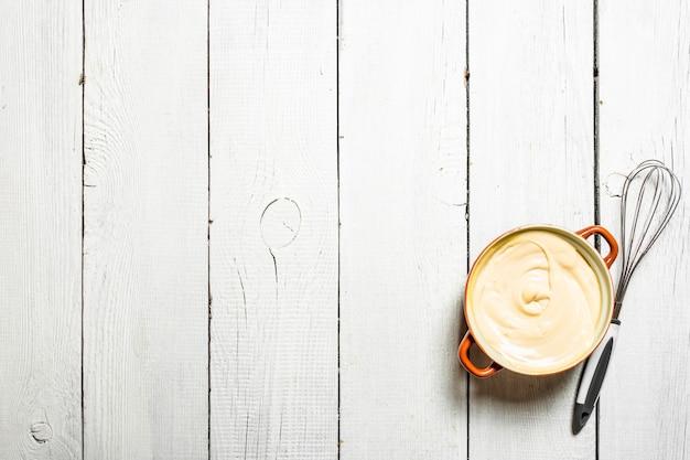 Mayonnaise dans un bol avec un fouet. sur une table en bois blanche.
