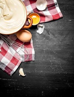 Mayonnaise fraîche avec les œufs et l'huile d'olive. sur un tableau noir.