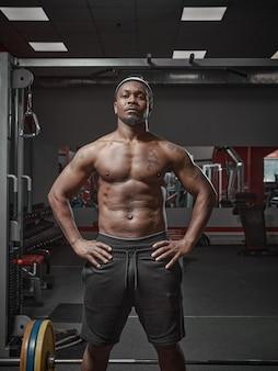 Mec afro-américain athlétique musclé avec torse nu posant sur l'entraînement en salle de gym