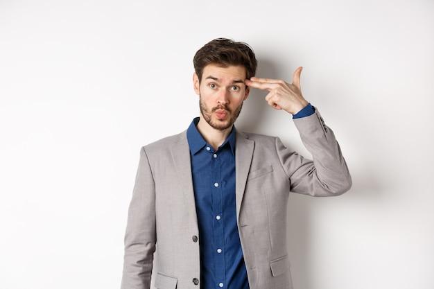 Un mec agacé en costume d'affaires se tire avec un pistolet près de la tête