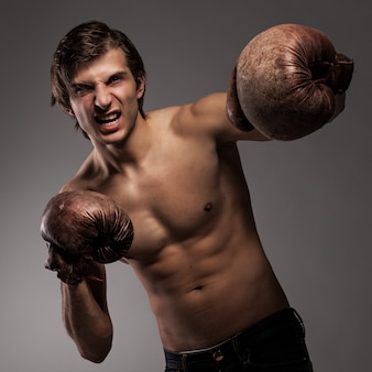 Mec agressif dans un gants de boxe