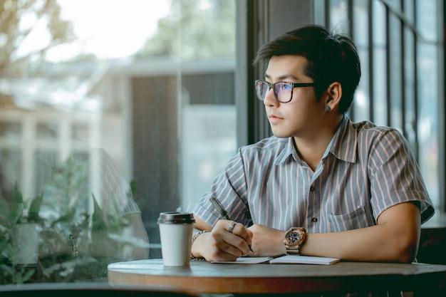 Mec asiatique avec des lunettes assis et écrit quelque chose avec pensée.