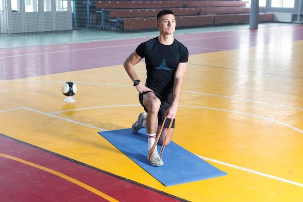 Mec athlétique en vêtements de sport et fitness tracker faisant des exercices dans la salle de gym.