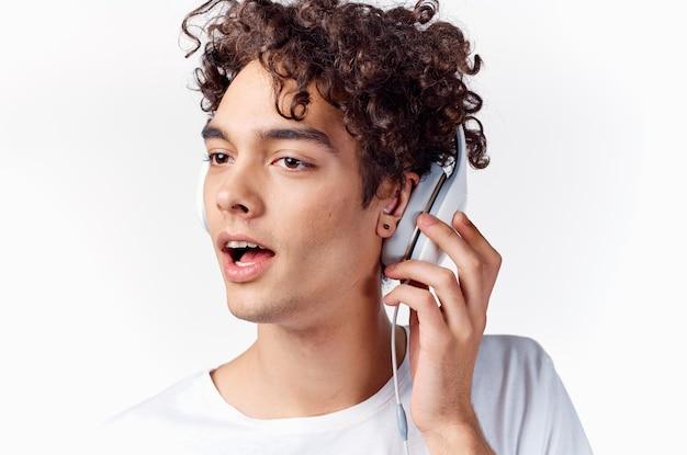 Mec aux cheveux bouclés dans les écouteurs à écouter de la musique vue recadrée émotion