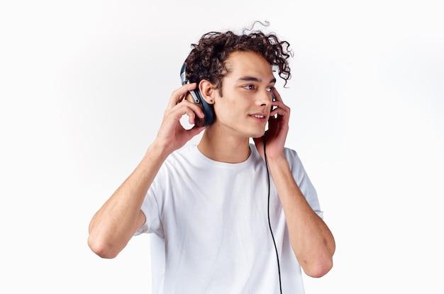 Mec aux cheveux bouclés en t-shirt blanc avec casque musique technologie divertissement
