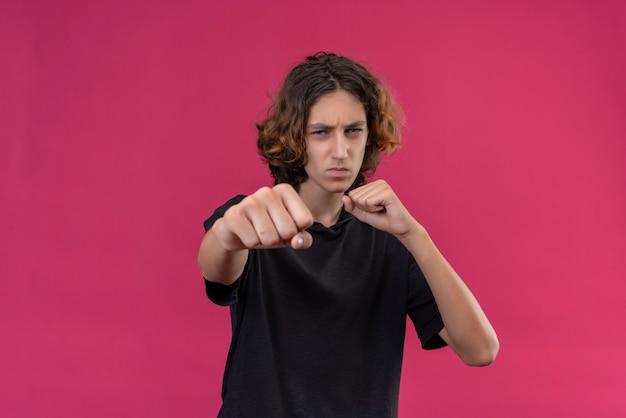 Mec aux cheveux longs en t-shirt noir montrer le poing sur le mur rose