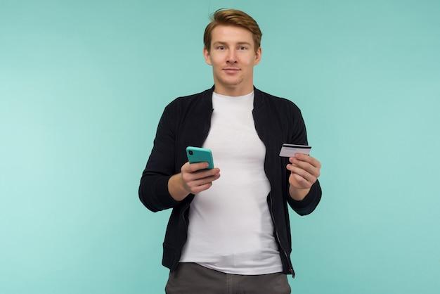 Un mec aux cheveux roux sportif gai effectue un paiement en ligne et regarde l'écran du smartphone sur un espace bleu.