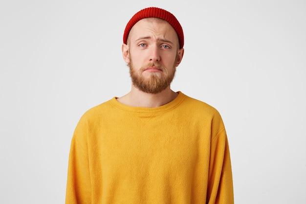 Mec aux yeux bleus attristés, vêtu d'un chapeau rouge et d'un pull jaune.