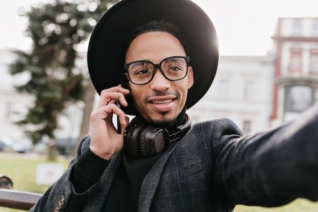 Mec aux yeux sombres dans des écouteurs faisant selfie dans le parc. homme africain élégant appelant quelqu'un tout en prenant une photo de lui-même.