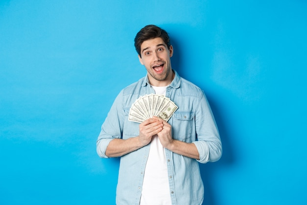 Un mec avide souriant embrassant de l'argent et souriant, ne voulant pas partager, debout sur fond bleu.