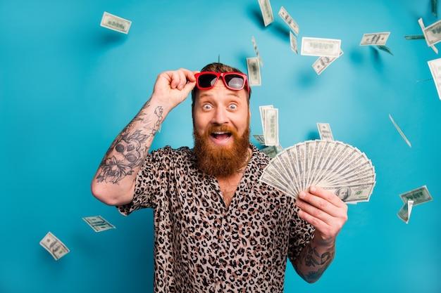 Un mec barbu au gingembre excité et drôle tient un ventilateur en argent