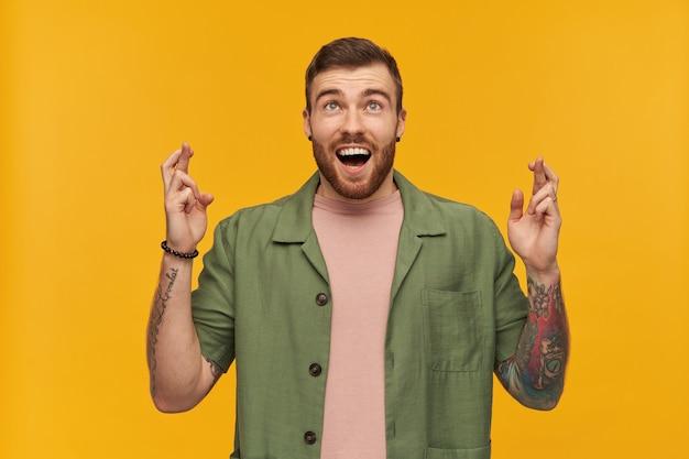 Mec barbu, homme à la recherche heureux avec des cheveux bruns. vêtu d'une veste verte à manches courtes. a des tatouages. croise les doigts, fait un vœu. regarder à copie espace, isolé sur mur jaune