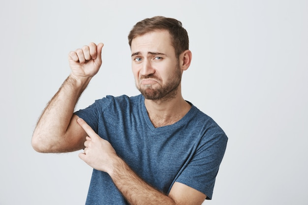 Un mec barbu mécontent plie des biceps faibles, a besoin d'aller à la gym