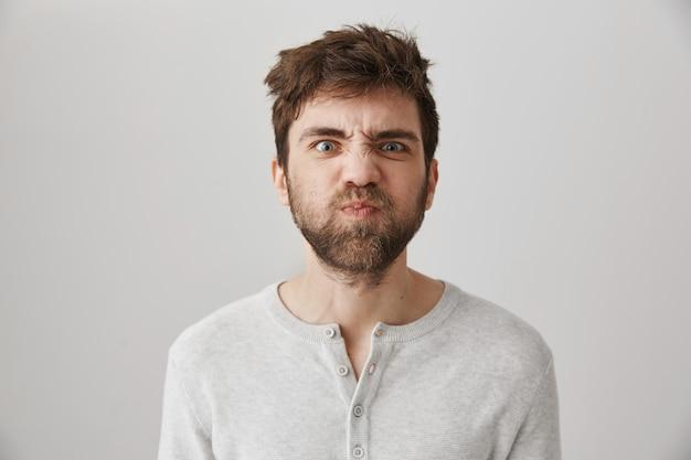Mec barbu moue avec les cheveux jetés grimaçant