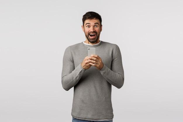 Mec barbu en pull gris à l'aide de smartphone