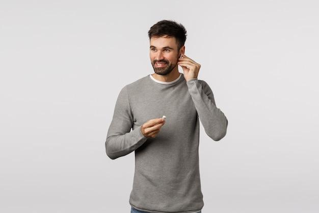 Mec barbu en pull gris mettant des écouteurs sans fil