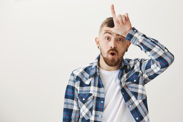Mec barbu se moquant de quelqu'un avec un geste de perdant