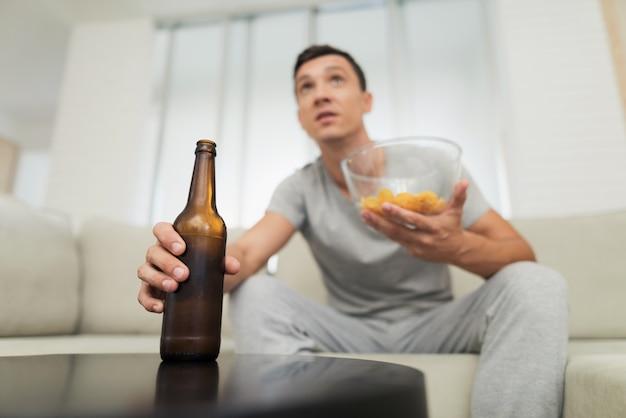 Mec avec de la bière et des frites en regardant la télévision.