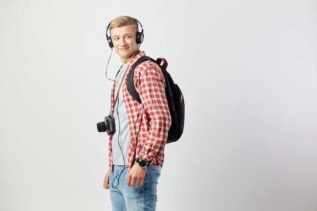 Mec blond avec sac à dos et appareil photo numérique vêtu d'une chemise à carreaux rouges et d'un jean