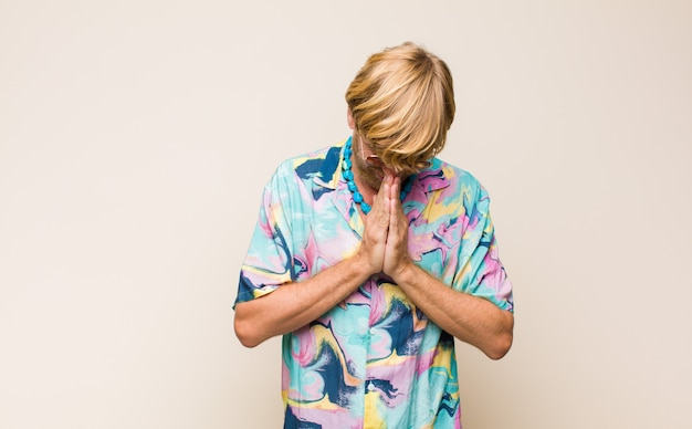 Mec blond se sentant inquiet, plein d'espoir et religieux