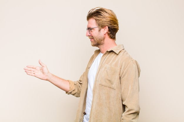 Mec blond souriant et offrant une poignée de main