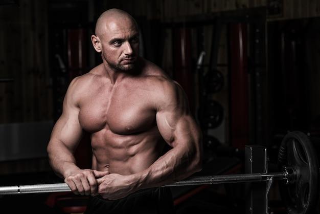 Un mec bodybuilder musculaire attrayant se prépare à faire des exercices avec la barre dans une salle de gym. guy bodybuilder fatigué en gymnase. bodybuilder jeune homme se reposant en gymnase après l'exercice