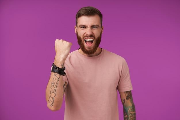 Mec brune barbu excitée avec des tatouages criant joyeusement et levant le poing en signe oui, fronçant les sourcils avec la bouche grande ouverte, posant sur le violet dans des vêtements décontractés et des accessoires à la mode